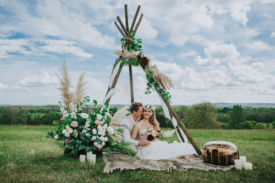 Couplekissing in front of a naked tipi ceremony set up