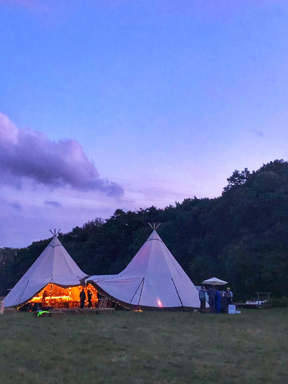 Two tipis at dusk, lit up from the inside