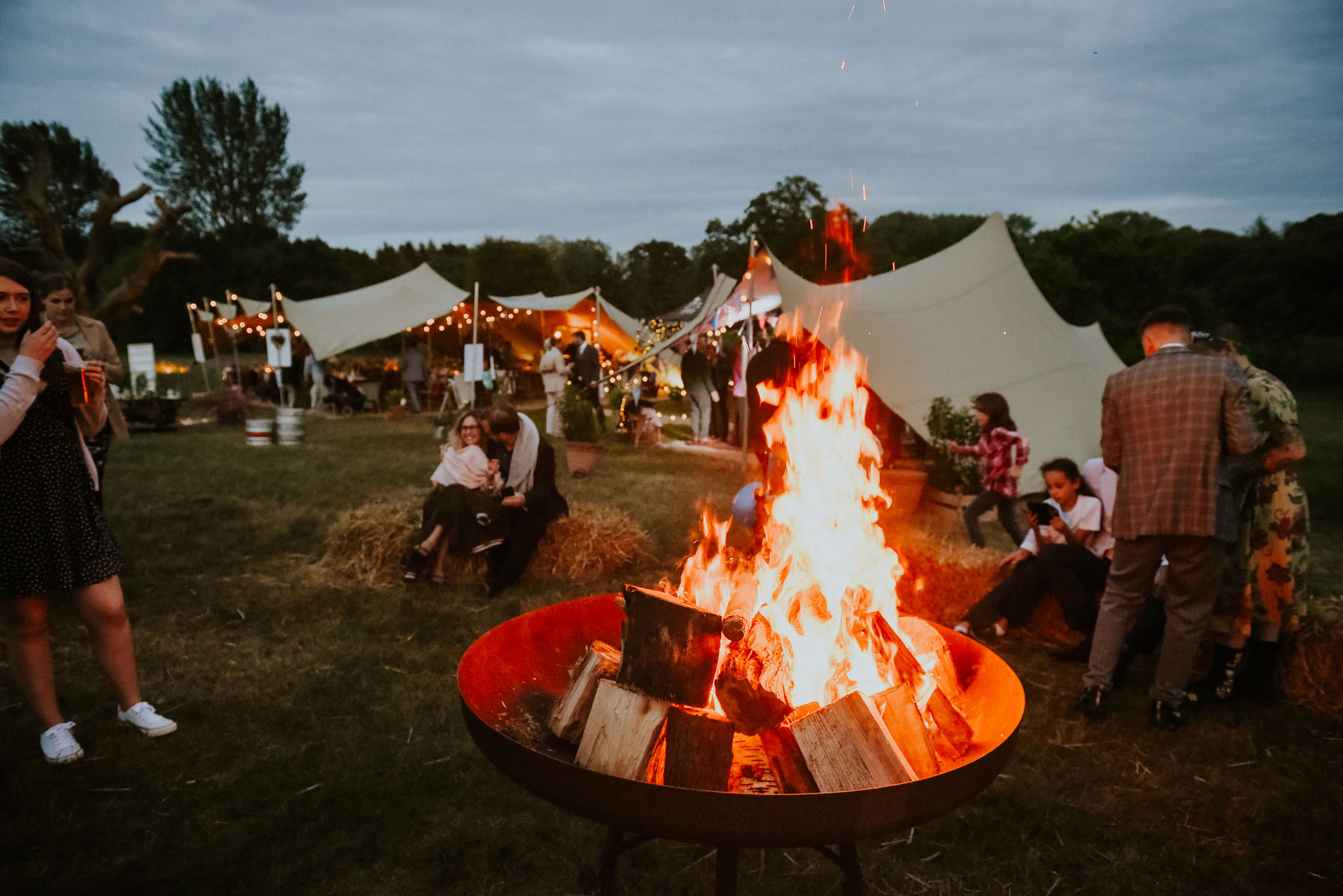stretch tents behind group around a firepit