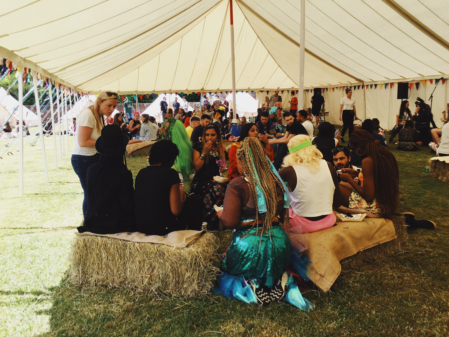 people sitting on hay bales in a marquee