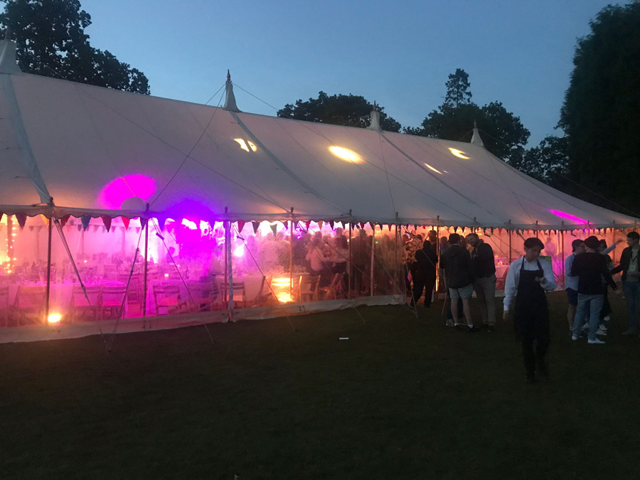 Marquee seen from outside, lit up with coloured lights