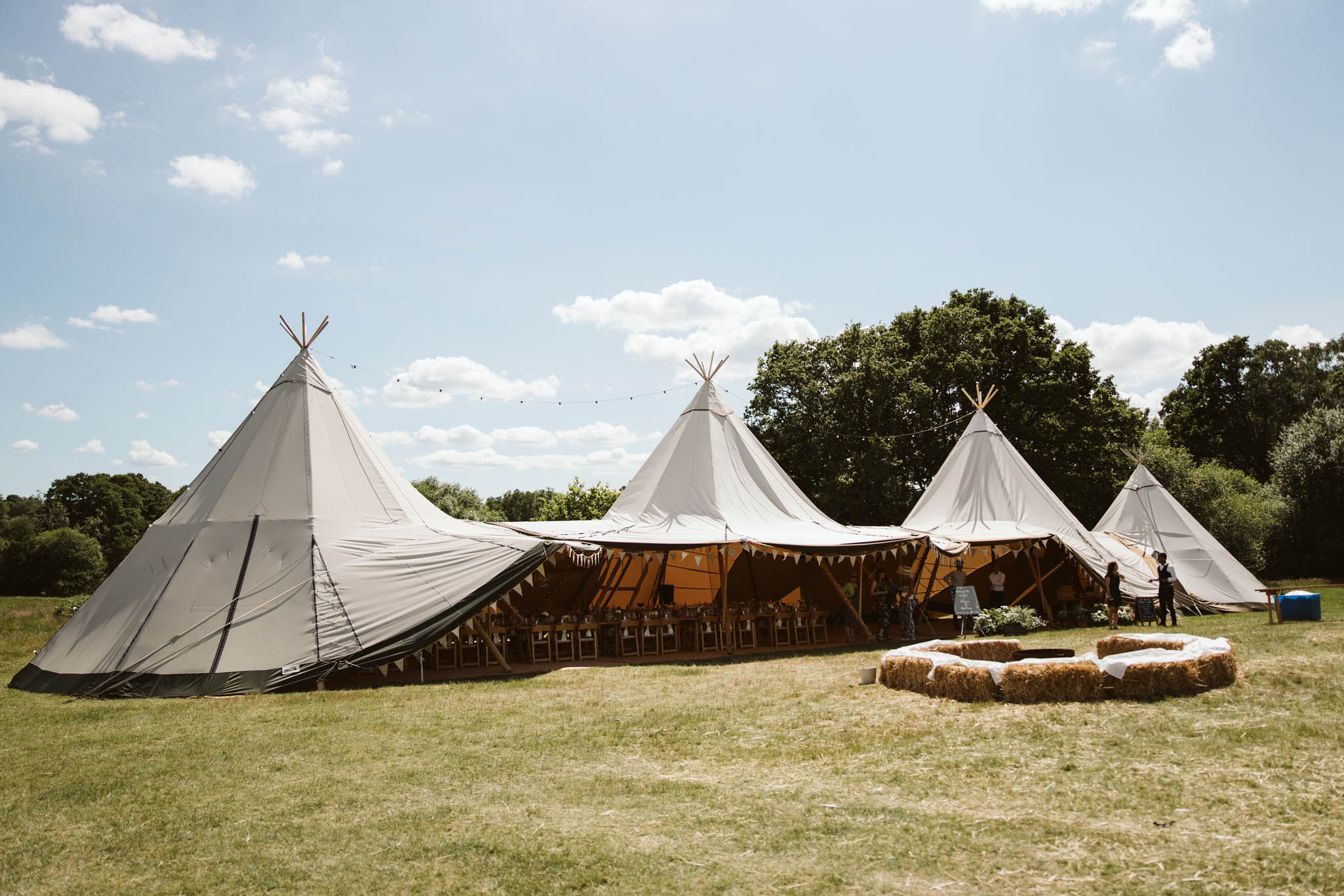 off-white tipis in a field