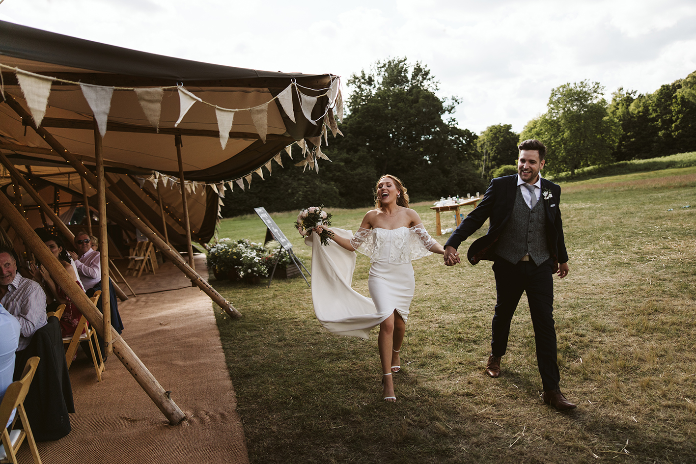 bride and groom making their way into their tipi reception