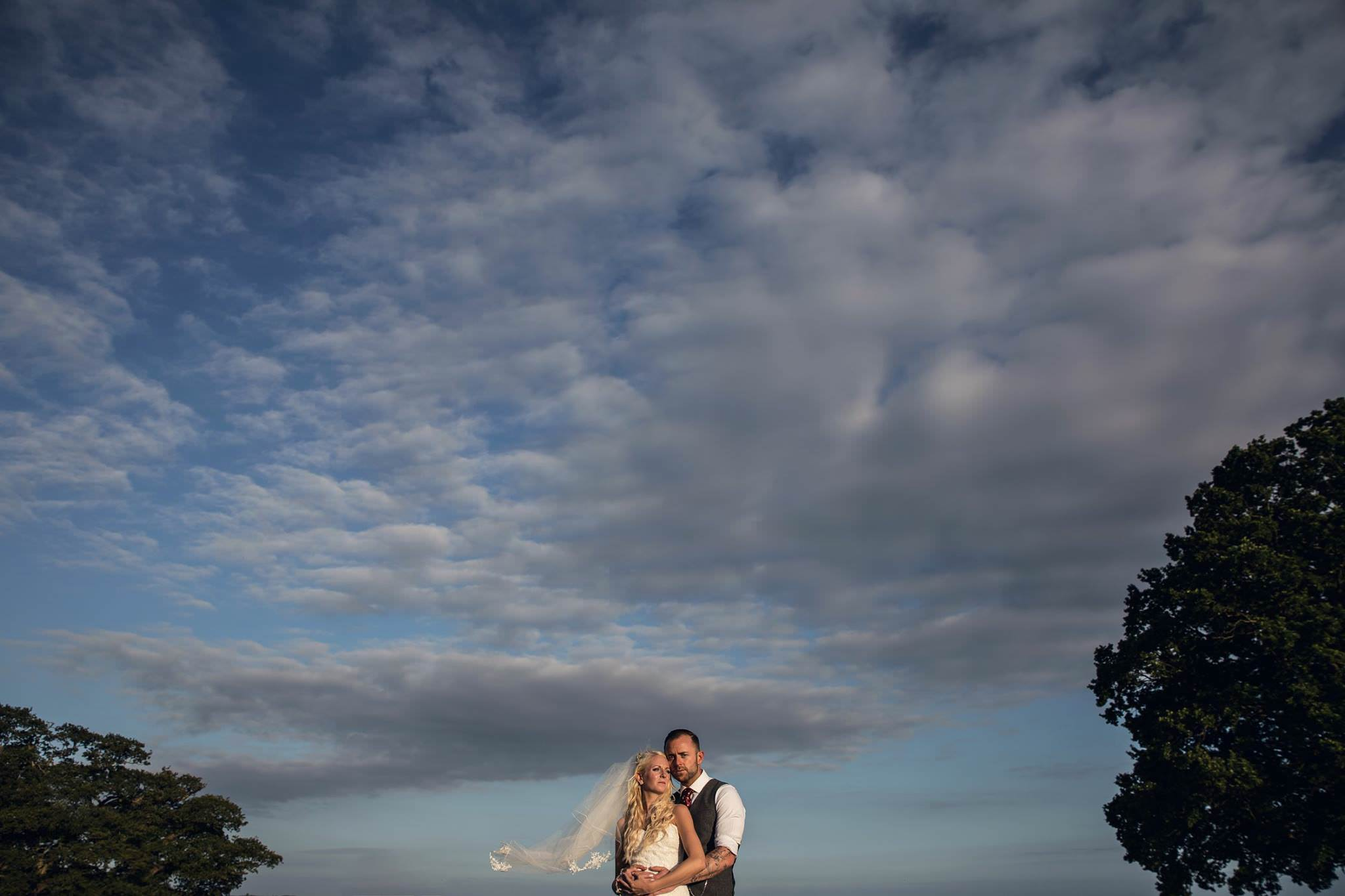 couple up close with big skies and clouds behind them