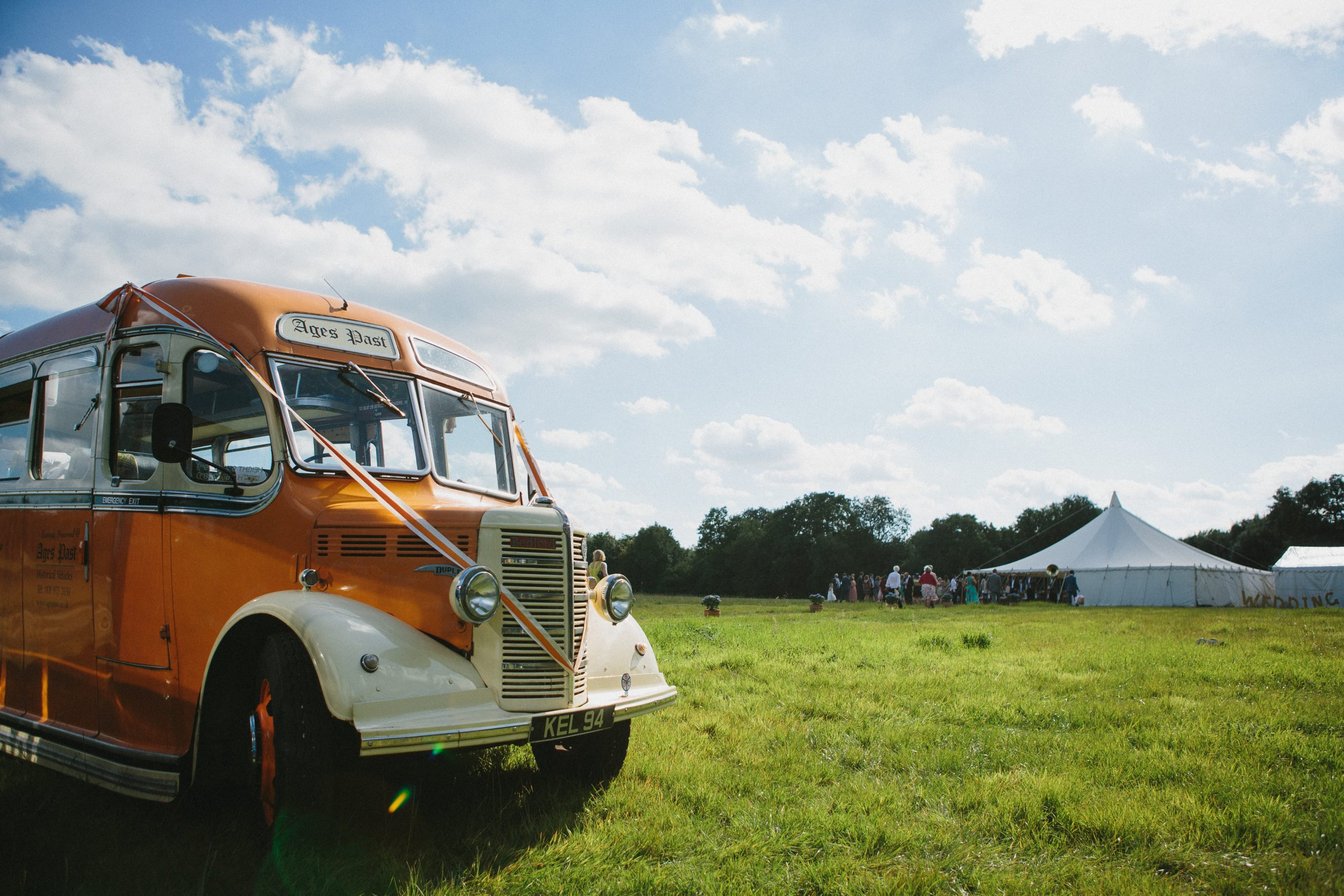 vintage bus in front of a traditional pole tent in a field