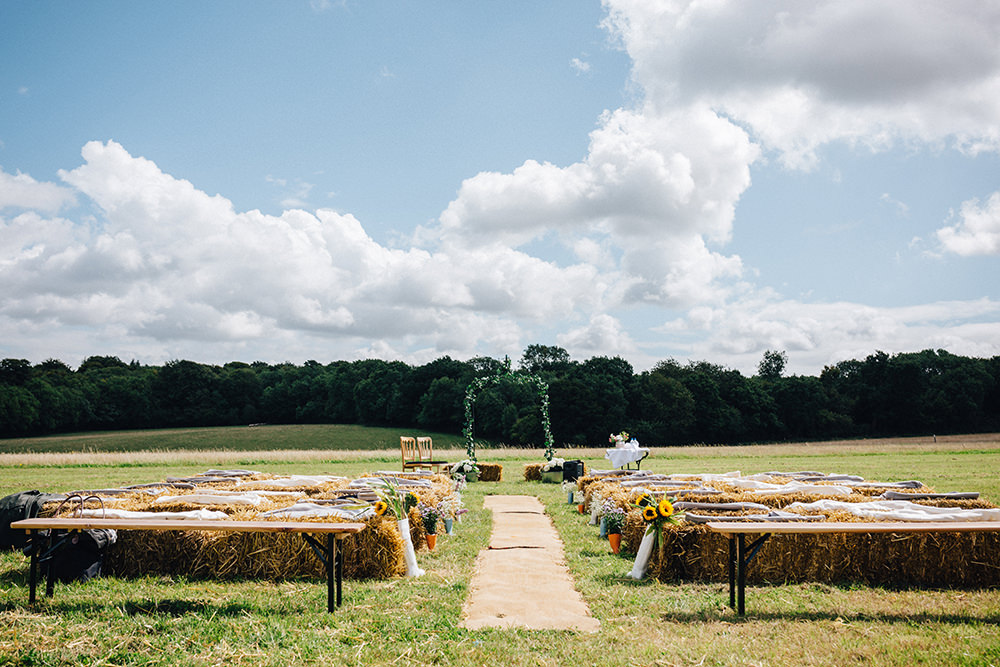 hay bales set up for an outdoor ceremony in a field