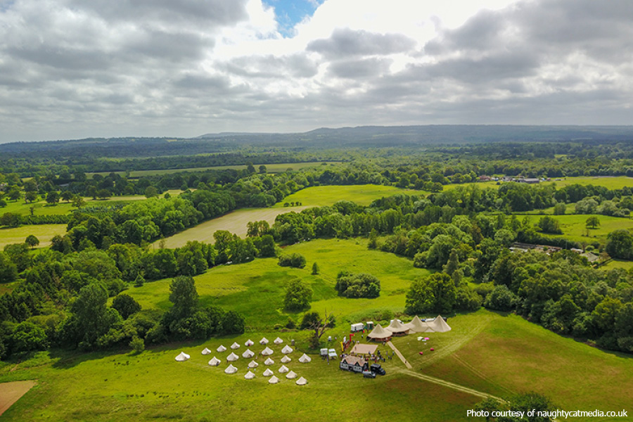 drone shot of a field wedding with tipis and bell tents