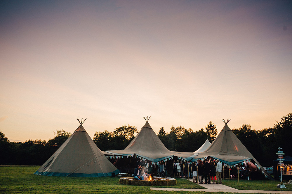 tipis in a field at sunset