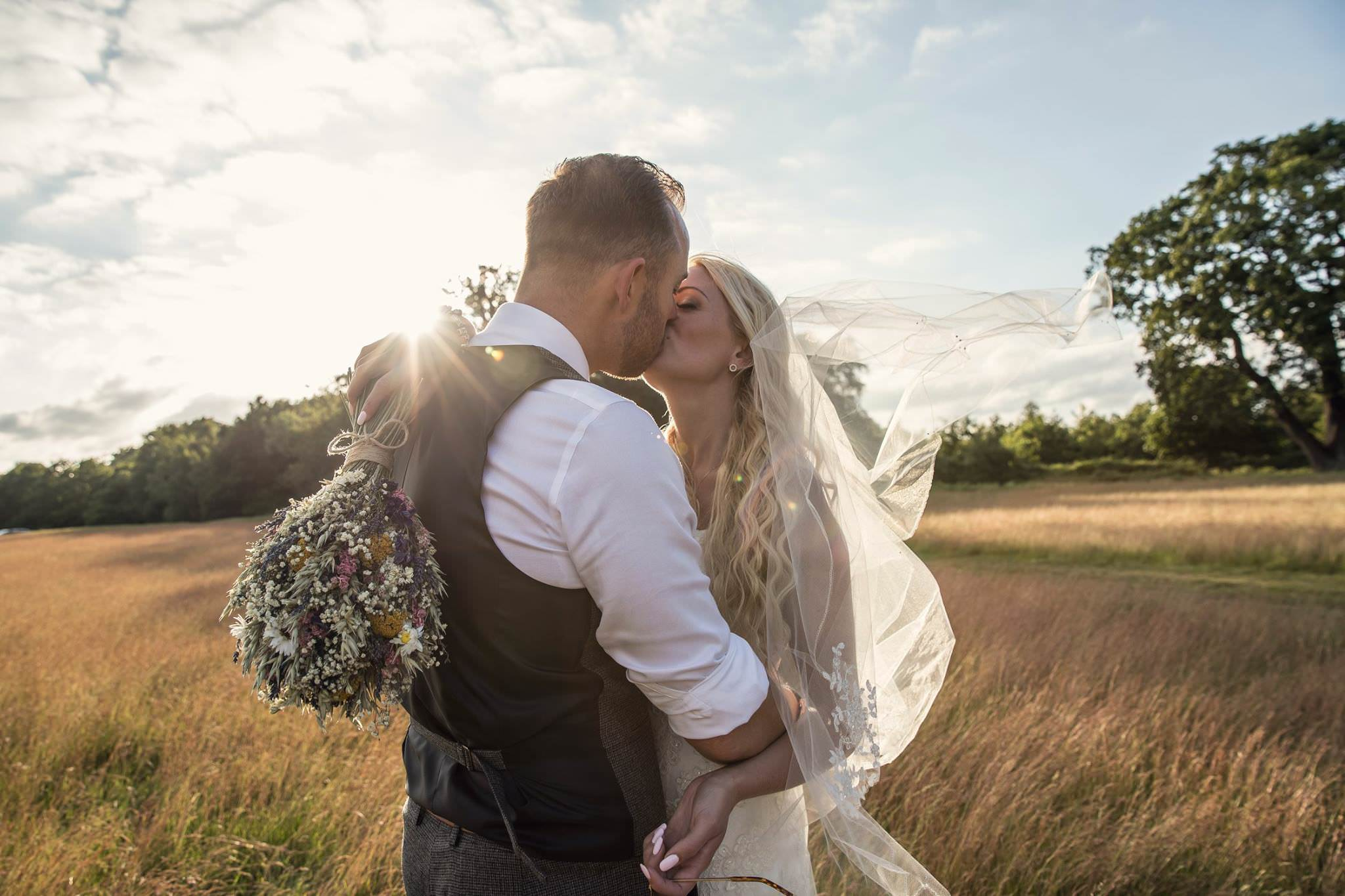 bride and groom kissing in a beautiful field at magic hour
