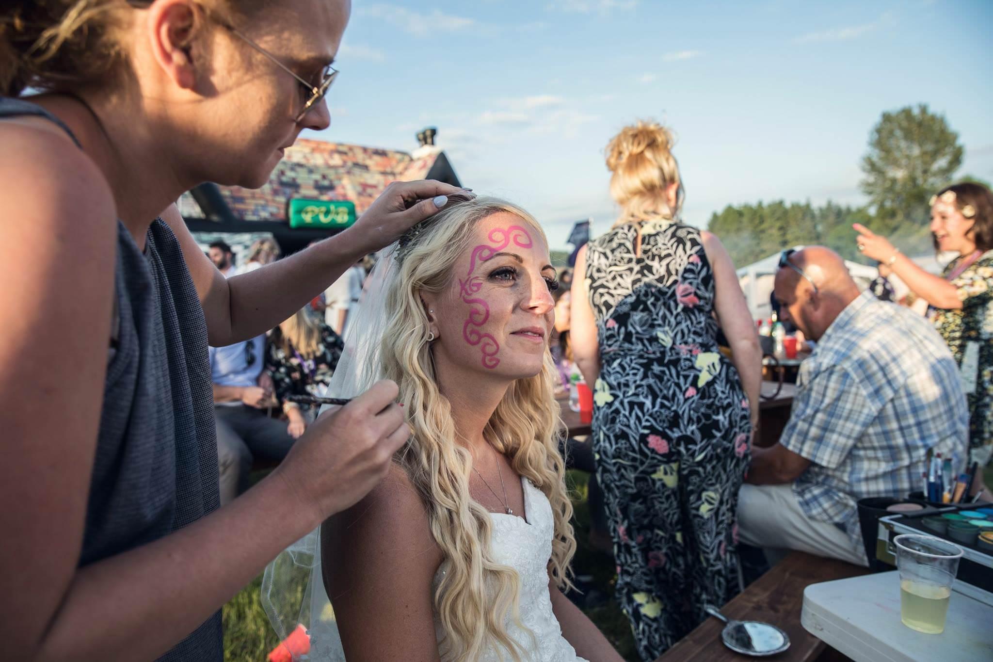 bride having festival face paint at her festival wedding fiesta fields