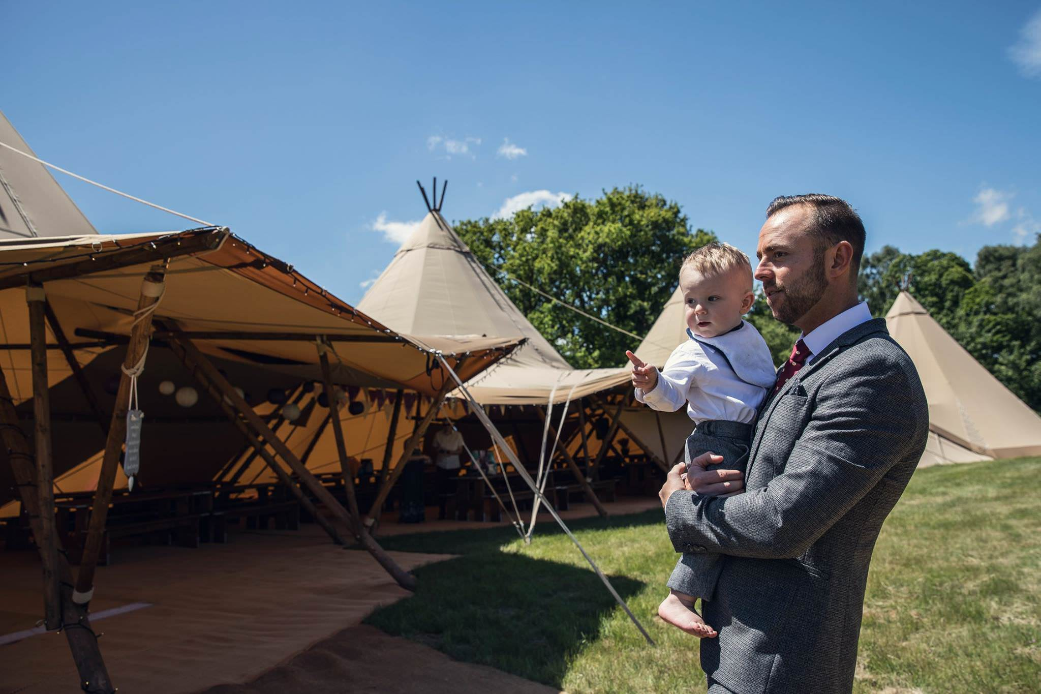 groom with little boy outside tipis
