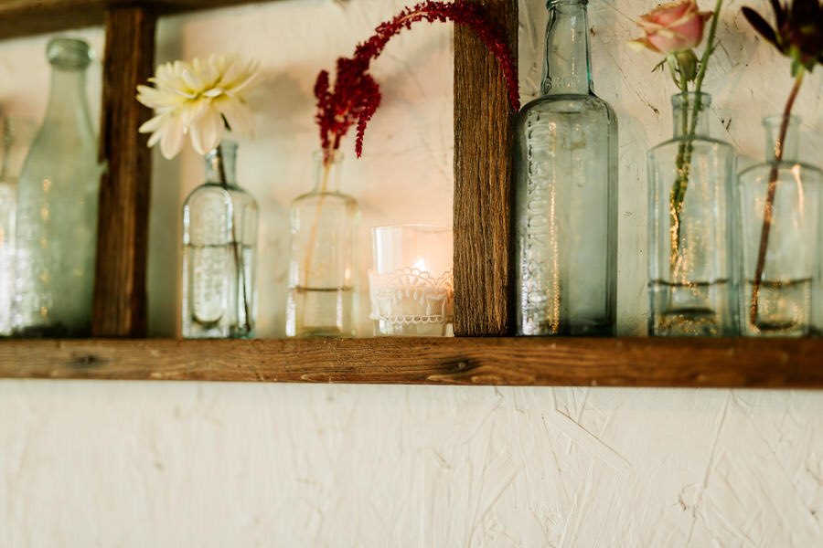 mismatched glass jars and vases on a rustic shelf