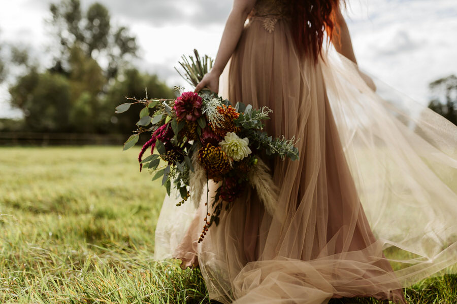 bride walking away in a field with red hair and autumnal bouquet