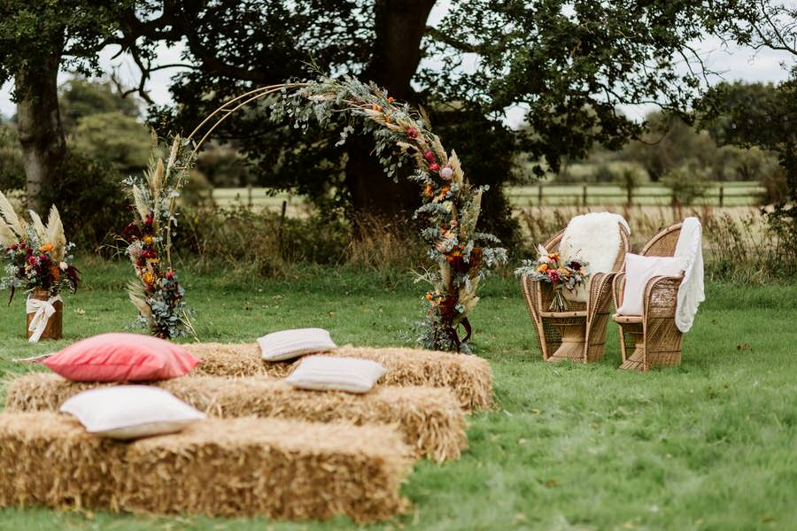 straw bales and moon arch at an outdoor wedding ceremony