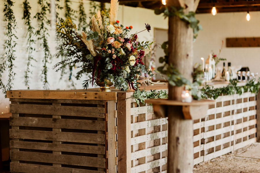 pallet bar decorated with foliage in rustic barn